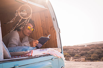 Spain, Tenerife, woman in parked van reading book - p300m1505399 by Simona Pilolla