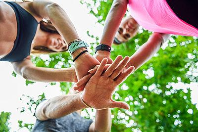 Young sports team stacking hands, celebrating success - p300m2060704 von Javier Sánchez Mingorance
