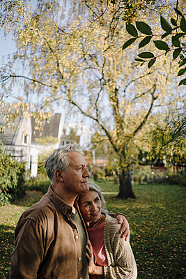 Senior couple in garden of their home in autumn - p300m2156228 by Gustafsson