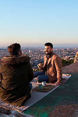 Gay couple talking while having breakfast on observation point, Bunkers del Carmel, Barcelona, Spain - p300m2257334 by Veam