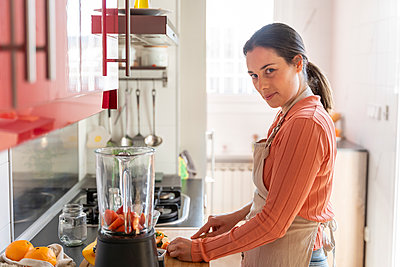 Young woman cutting strawberry on board in kitchen at home - p300m2264478 by VITTA GALLERY