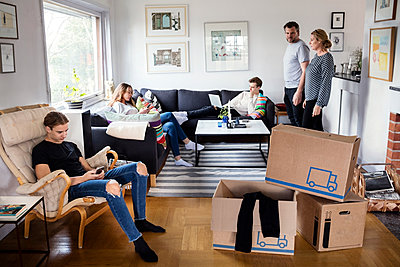 Parents looking at siblings sitting in living room with cardboard boxes - p426m1179599 by Maskot