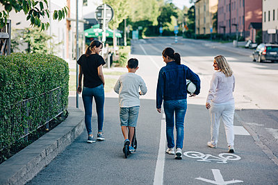 Rear view of family walking on bicycle lane street in city during sunny day - p426m1517895 by Maskot