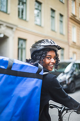 Portrait of smiling delivery woman with bag in city - p426m2145396 by Maskot