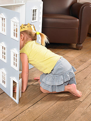 Little girl playing with a doll house - p4292516f by Ghislain & Marie David de Lossy