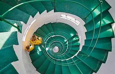 Overhead view of mother and son on spiral staircase, Tavares, Rio Grande do Sul, Brazil, South America - p429m1519608 by Stephen Lux