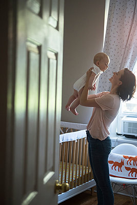 Caucasian mother holding baby son face to face in bedroom - p555m1303868 by JGI/Jamie Grill