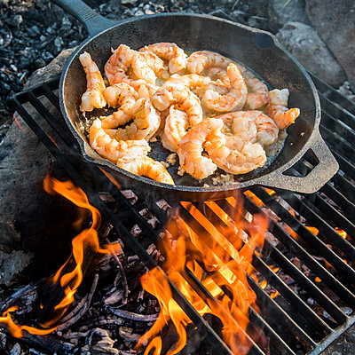 Shrimp frying in skillet over campfire - p555m1532709 by Steve Smith
