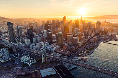 Aerial of downtown district at sunset with Bay bridge in the foreground, San Francisco, California, USA - p651m2007181 by Matteo Colombo photography