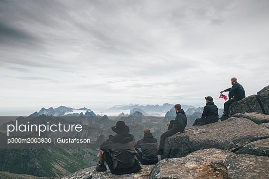Norway, Lofoten, Moskenesoy, Young men sitting at Hermannsdalstinden, looking over Kjerkefjord - p300m2003930 von Gustafsson
