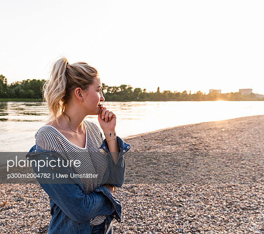 Young blond woman waiting on riverside in the evening - p300m2004782 von Uwe Umstätter