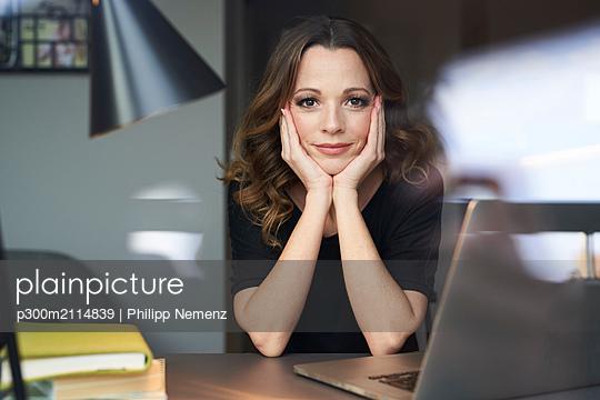 Portrait of woman with laptop behind windowpane - p300m2114839 von Philipp Nemenz