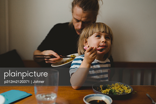 Father and daughter having meal - p312m2120371 by Johner