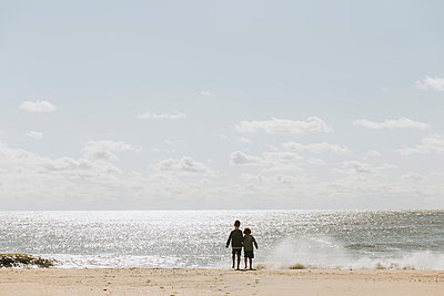 Rear view of brothers standing at shore against sky during sunny day - p1166m2034793 by Cavan Images