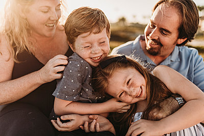 Close up detail of family of four playing during sunset at beach - p1166m2136580 by Cavan Images
