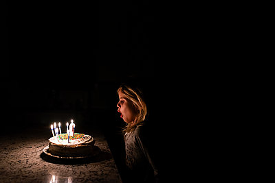 Little girl blowing out birthday cake candles - p1166m2201757 by Cavan Images