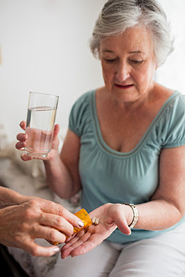 Nurse giving medicaments to a senior woman in a retirement home - p1315m1186282 by Wavebreak