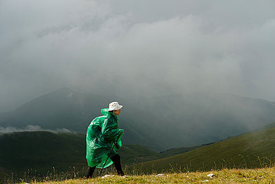 Woman hiker in green raincoat, Caucasus Mountains - p1363m2063260 by Valery Skurydin