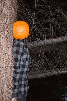 Man with a pumpkin in his head, lying down on the forest - p1423m2210963 by JUAN MOYANO