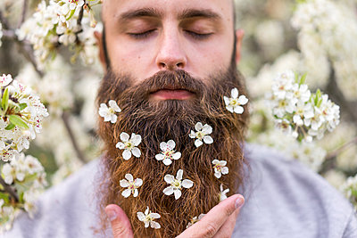 Portrait of hipster with white tree blossoms in his beard - p300m1581437 von VITTA GALLERY