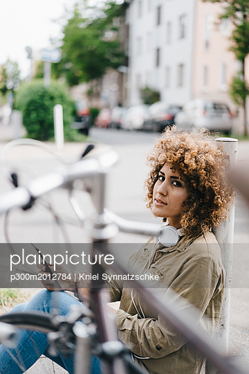 Woman in the city with headphones, using smartphone - p300m2012784 von Kniel Synnatzschke