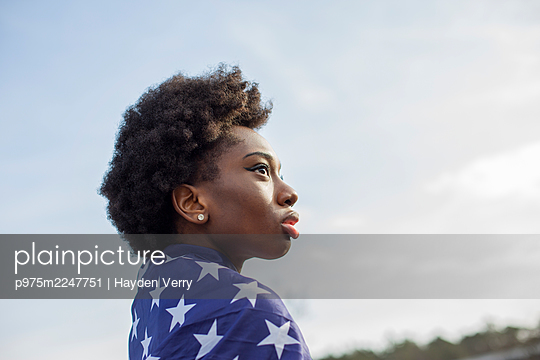 Woman with black ethnicity wrapped in American flag - p975m2247751 by Hayden Verry