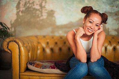 Portrait smiling, confident young woman sitting on sofa - p1023m2046821 by Paul Bradbury