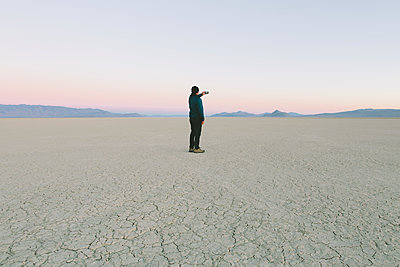 Man taking photo with smart phone, standing in vast desert playa, Black Rock Desert, Nevada - p1100m1216327 by Mint Images