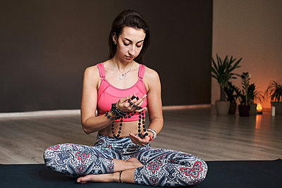 young woman meditating alone with a yoga studio for yoga with beads - p1166m2177394 by Cavan Images