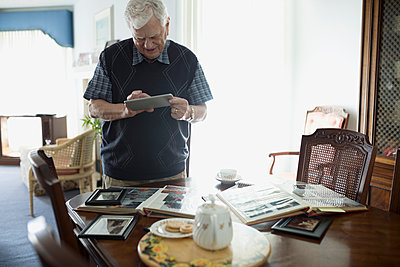 Senior man using digital tablet at dining table with photograph albums - p1192m1145509 by Hero Images