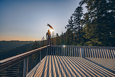 Man is standing on top of a guard rail, facing a sunset while holding up a longboard - p1455m2092372 von Ingmar Wein