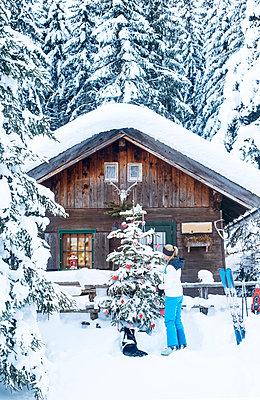 Austria, Altenmarkt-Zauchensee, woman decorating Christmas tree at hut - p300m2060155 by Hans Huber