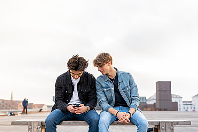 Denmark, Copenhagen, two young men sitting on a bench using cell phone - p300m2102154 von VITTA GALLERY