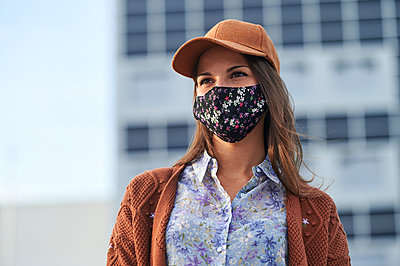 Young woman wearing cap and face mask looking away while standing in city - p300m2221104 by Kiko Jimenez