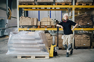 Full length of confident worker standing by stacked planks on pallet jack at industry - p426m1537055 by Maskot