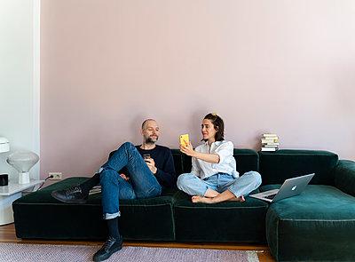 Paar verbringt zusammen Zeit auf dem Sofa - p432m2176122 von mia takahara