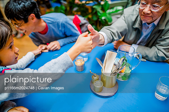 Grandson and grandfather playing thumb wrestling at restaurant - p1166m2024748 by Cavan Images