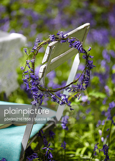 Bluebell garland on chair back in woods - p349m2167858 by Sussie Bell
