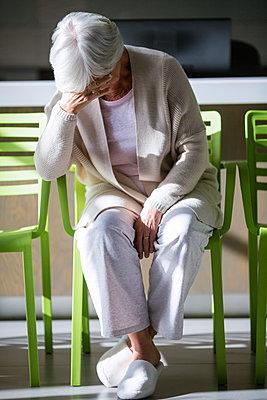 Tensed senior woman sitting on chair in waiting area - p1315m1227965 by Wavebreak