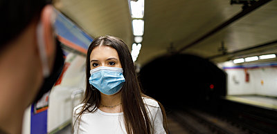 Young woman wearing face mask looking at man while standing at subway station - p300m2226462 by Ignacio Ferrándiz Roig