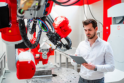 Young man using digital tablet by robotics in factory - p300m2265152 by Daniel Ingold