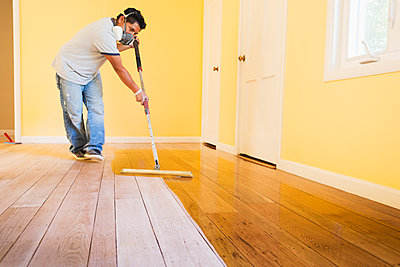Hispanic man refinishing floors in new house - p555m1408521 by Sollina Images