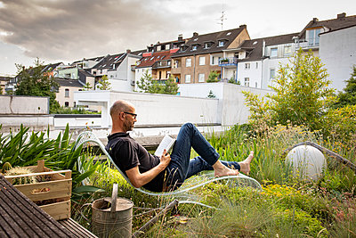 Man in deck chair on rooftop reading a book - p948m2222837 by Sibylle Pietrek