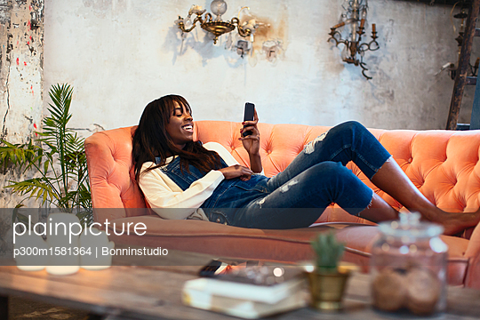 Laughing woman lying on the couch at home using cell phone - p300m1581364 von Bonninstudio