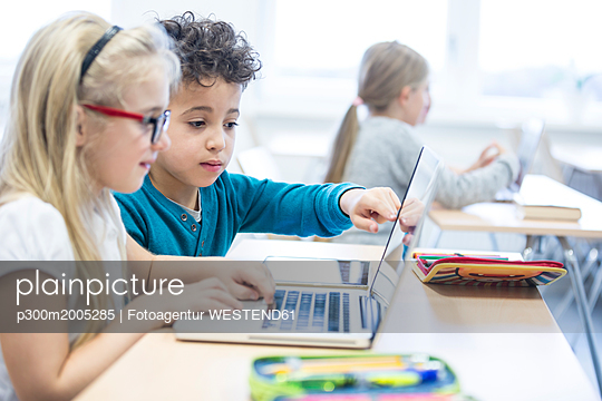 Schoolboy and schoolgirl using laptop together in class - p300m2005285 von Fotoagentur WESTEND61