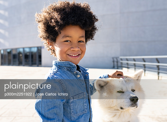 Smiling boy playing with dog while standing outdoors - p300m2251922 by Jose Carlos Ichiro