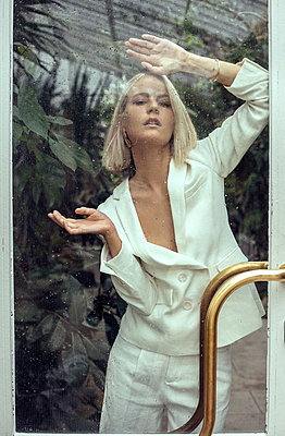 Fashion portrait of young woman standing behind glass door - p1166m2124044 by Cavan Images