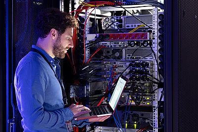 Male IT specialist working on laptop in server room - p300m2274457 by Florian Küttler