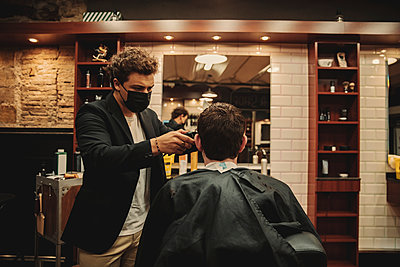 Male barber wearing protective face mask cutting customer's hair in salon - p300m2287156 by Aitor Carrera Porté