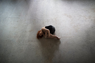 Caucasian woman laying on concrete in fetal position - p555m1523131 by Kateryna Soroka